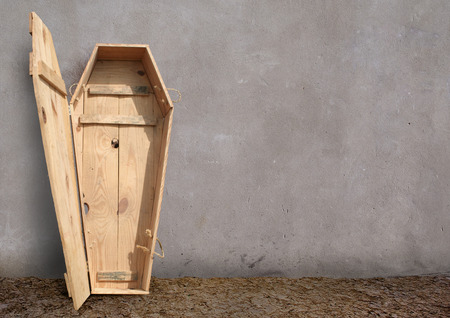 灰色の壁の屋外、シンプルな棺です。