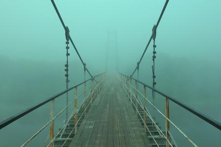 霧の中に、川に架かる吊り橋。 写真素材