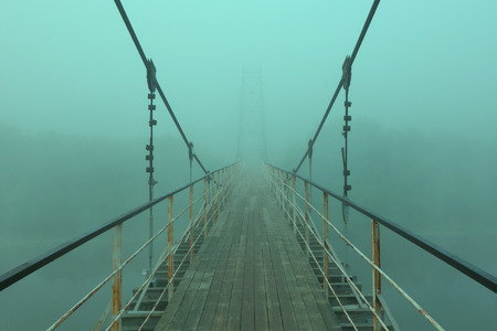 suspension bridge: Suspension bridge over the river,during fog.