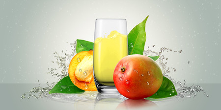 frutas tropicales: Un vaso de jugo de mango con frutos de mango. Foto de archivo