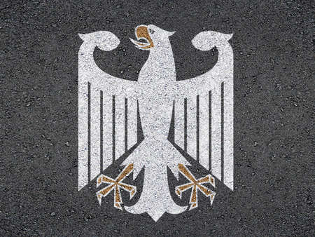 cliche: The coat of arms of Germany on asphalt.