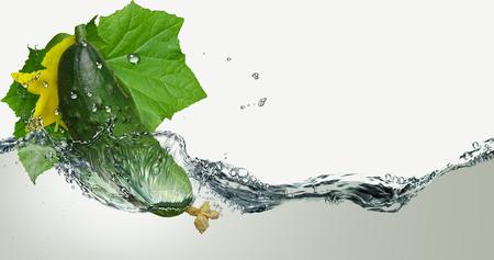 Fresh cucumber in spray of water.