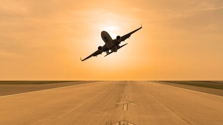 Plane taking off from the runway at sunset day 写真素材