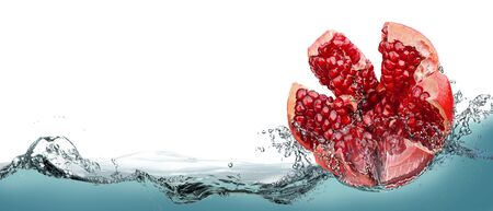 Pomegranate fruit in spray of clean water.