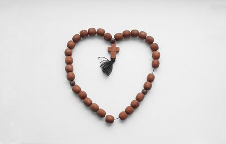 Rosary Christian mahogany with a cross on an isolated background.