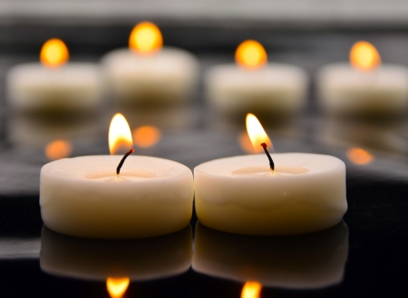 White burning candles on blurred out background photo
