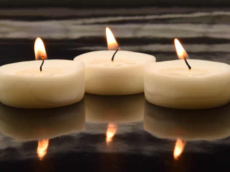 mirroring: three small tea lights on a black, mirroring surface Stock Photo