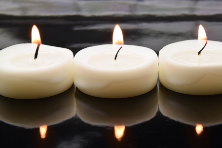 three small tea lights on a black, mirroring surface photo