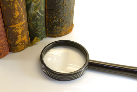 antiquarian: closeup of old books from an antiquarian bookshop with magnifier Stock Photo
