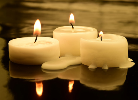 three small tea lights in the dark Stock Photo