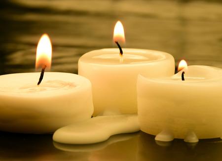 three small tea lights in the dark photo