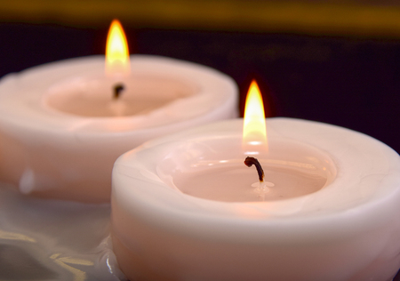 closeup of white burning candles on black background Stock Photo - 27384228