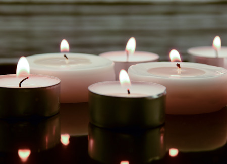 obituary: three small tea lights on a black, mirroring surface Stock Photo
