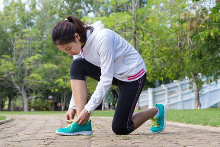 shoe laces: Running woman. Female runner tying shoe laces during outdoor workout. Stock Photo