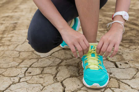runner: Running woman. Female runner tying shoe laces during outdoor workout. Stock Photo