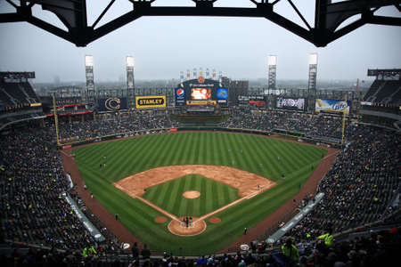 outfield: Chicago, Illinois - April 25, 2010: White Sox baseball players under the lights at U.S. Cellullar Field, including the upper deck facade Editorial