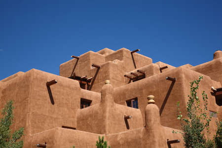 adobe pueblo: Adobe Building - Southwest adobe style architecture with a bright blue sky in Santa Fe, New Mexico.