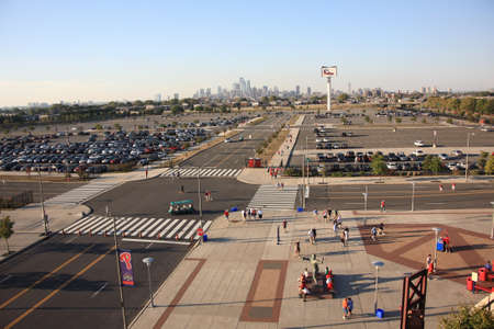 Philadelphia, Pennsylvania - September 7, 2010: Fans arrive for a late season baseball game at  the sports complex, with the Philadelphia skyline behind them.