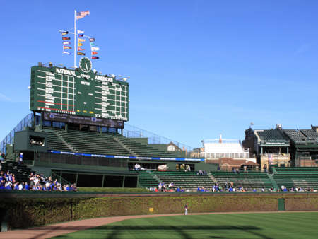 outfield: Chicago, Illinois - April 26, 2010: Famous scoreboard and outfield wall ivy at Wrigley Field, home of the Chicago Cubs.
