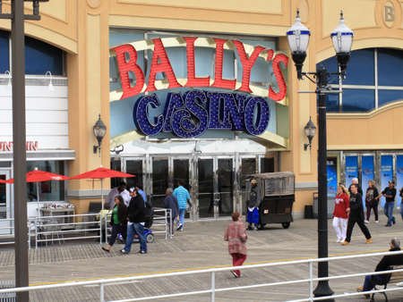 Atlantic City, New Jersey - May 19, 2010: Ballys Casino Hotel at the New Jersey shore, with people walking on famous boardwalk.