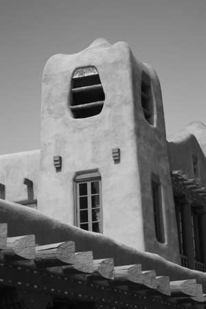 adobe pueblo: Adobe Building - Southwest adobe style architecture with a bright sky in Santa Fe, New Mexico. Black and white.