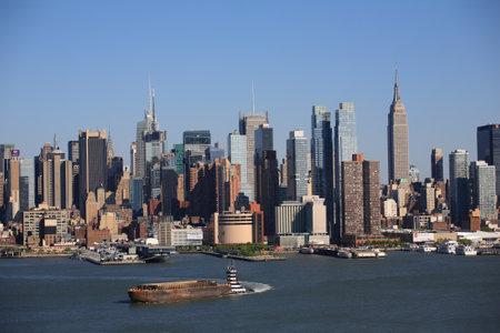New York - 29 april 2012: de skyline van Manhattan met een sleepboot en schip over de Hudson River.