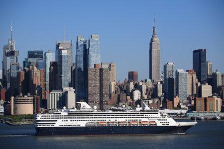 New York - April 29, 2012: The cruise ship Veendam passes the Manhattan city skyline.