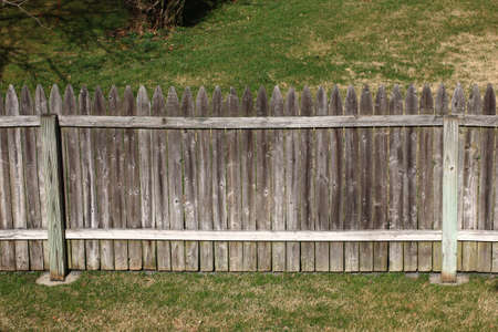 Picket Fence - Backyard fencing with wooden boards and green grass   photo
