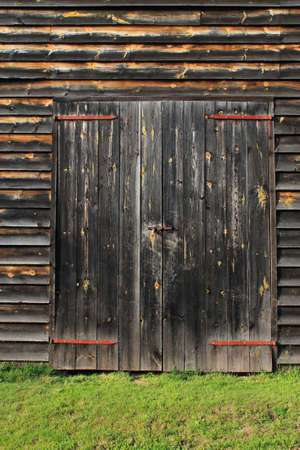 barn door: Barn Door Background - Closed barn doors on a farm building, with old weathered wooden planks