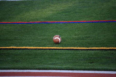 Football and Sidelines - A game ball rests on a turf grass field in between sideline markers. photo