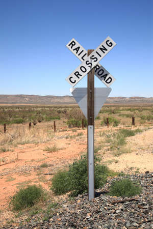 wood railroad: Railroad warning crossing sign on a rocky base in a desert landscape.