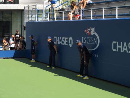 louis armstrong: Flushing, New York - September 3, 2014: US Open Linesman and lineswoman on a side court at the Billie Jean King Tennis Center.
