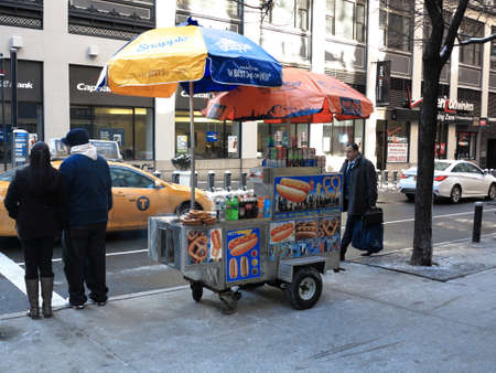 New York - March 6, 2015: A Manhattan hot dog stand with umbrellas. Editorial