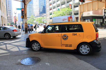 taxicab: Chicago, Illinois - June 18, 2012: A turning yellow taxicab in downtown Chicago.