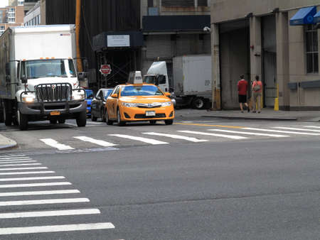 city road: New York - August 11, 2015: A NYC taxi at a crosswalk.