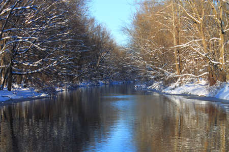 snow covered forest: Winter River - A snow covered forest with water reflections. Stock Photo