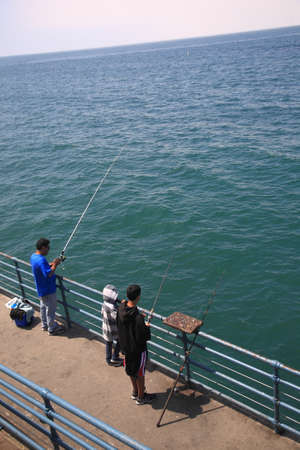 ocean fishing: Santa Monica, California - July 1, 2012: A family fishing on the Santa Monica Pier, with poles out over the Pacific Ocean.