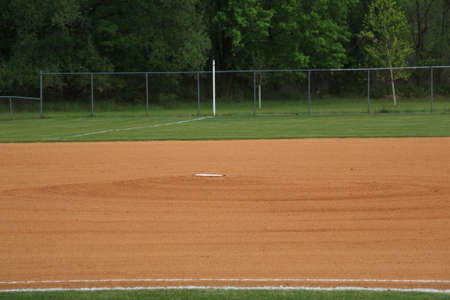 outfield: Baseball Infield - Baseball Pitching Rubber - Baseball field grassless infield pitching mound with rubber. With copy space.