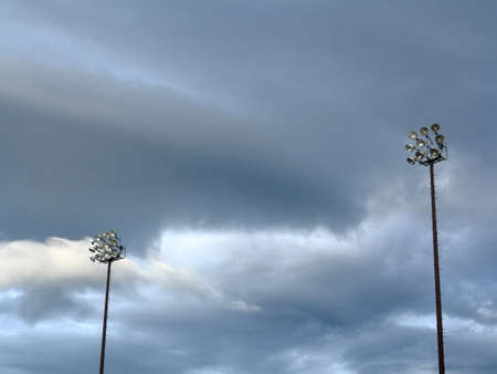 lighting background: Light Towers - Outdoor sports lighting and cloudy blue sky.