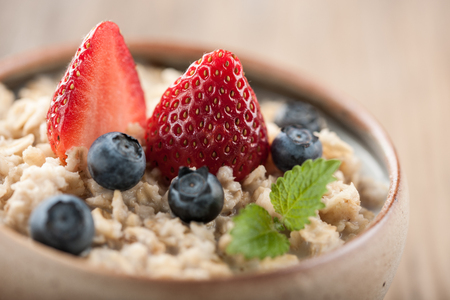 oatmeal bowl: Traditional oatmeal bowl topped with strawberries and blueberries