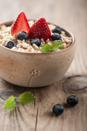 topped: Traditional oatmeal bowl topped with strawberries and blueberries