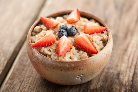 oatmeal bowl: Traditional oatmeal bowl topped with cut strawberries and blueberries