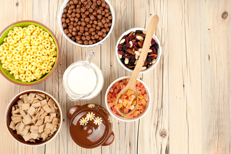 dried fruits: Mix cornflakes nuts milk  honey and dried fruits on wooden background