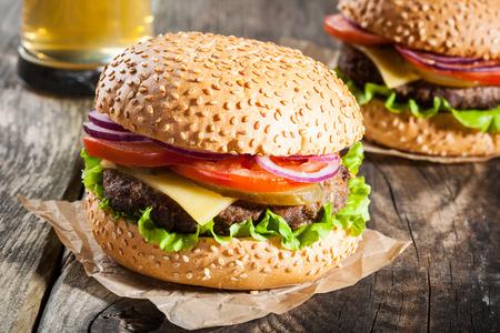 hamburguesa: Hamburguesas y un vaso de cerveza en la mesa de madera