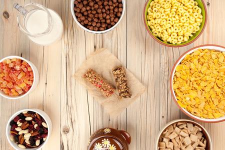 frutos secos: Mezclar los copos de maíz de miel leche nueces y frutos secos sobre fondo de madera