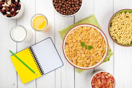 frutos secos: Mix Copos de maíz nueces miel zumo de naranja leche y frutos secos sobre fondo de madera