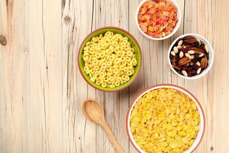 frutos secos: Mezclar los copos de maíz de miel y frutos secos sobre fondo de madera