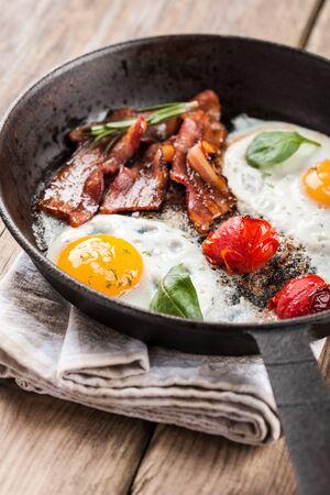 huevos estrellados: Huevos fritos con bacon y tomate en una sartén Foto de archivo