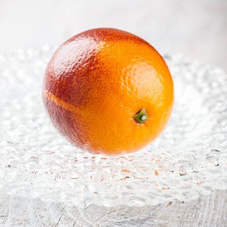 Fresh blood orange on glass plate