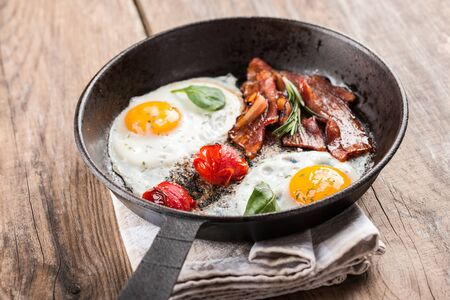 fried eggs: Fried eggs with bacon and tomato in a pan